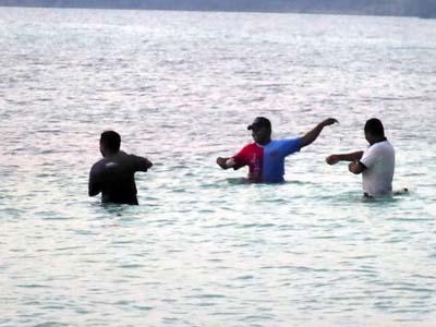 満ち潮で海水に浸かって釣りをする大人
