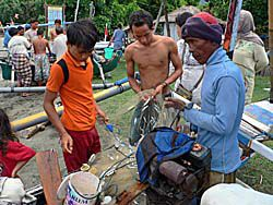 網にかかった小魚をとる人々